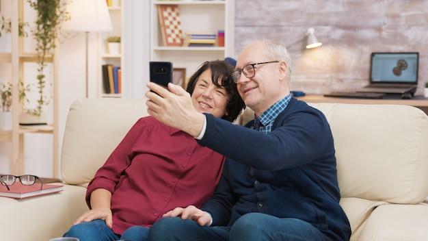 Szczęśliwa para starszych siedzi na kanapie i robi selfie w salonie