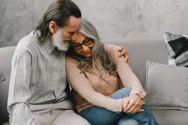 Szczęśliwa para starszych siedzi na kanapie w domu i rozmawia. pojęcie czasu jakości.