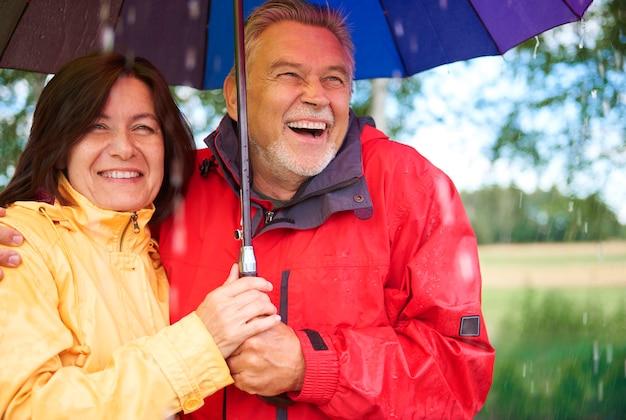 Szczęśliwa para starszych stojąca podczas deszczu