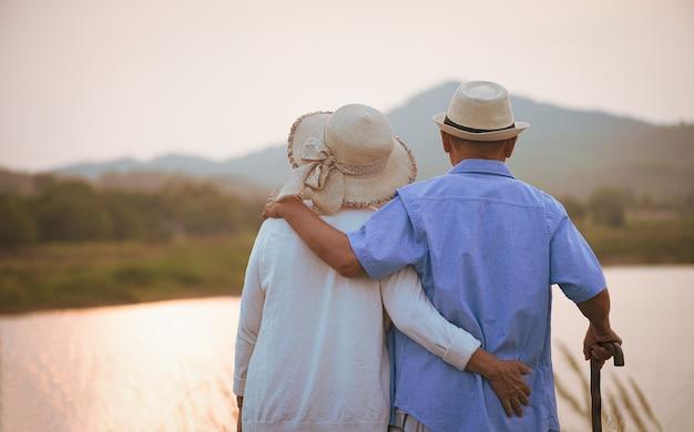 Szczęśliwa para starszych stojących w pobliżu góry i jeziora podczas zachodu słońca
