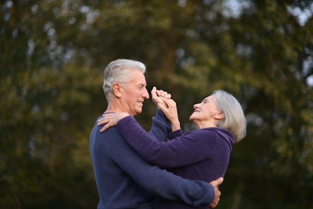 Szczęśliwa para starszych tańczy w letnim parku