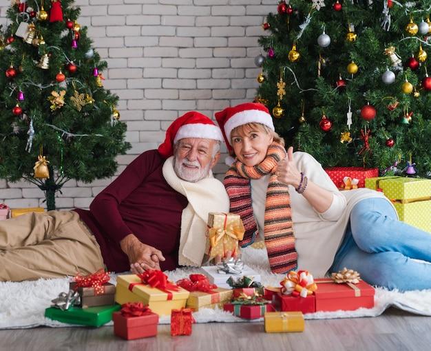 Szczęśliwa para starszych w kapeluszu świętego mikołaja ustanawiającego wraz z prezentami świątecznymi przed ozdobioną choinką w salonie. kobieta zadowolona z teraźniejszości. romantyczne ferie zimowe.