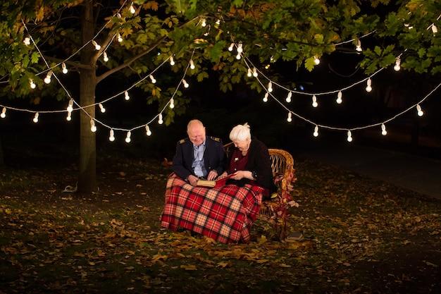 Szczęśliwa para starszych w parku, babcia i dziadek. spójrz na album ze zdjęciami.