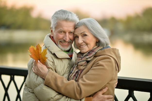 Szczęśliwa para starszych w pobliżu rzeki na jesieni, niewyraźne tło