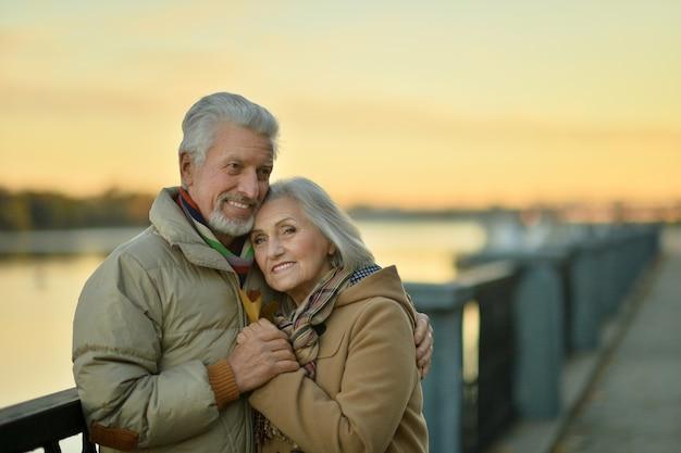 Szczęśliwa para starszych w pobliżu rzeki na jesieni