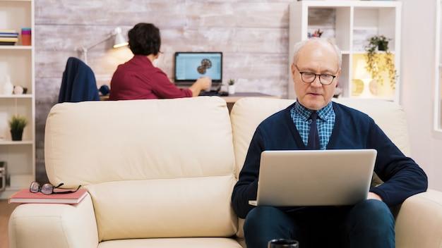Szczęśliwa para starszych w średnim wieku siedzi na kanapie, machając na laptopie podczas rozmowy wideo.
