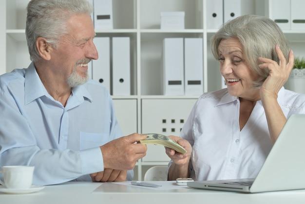 Szczęśliwa para starszych z laptopem i pieniędzmi w biurze