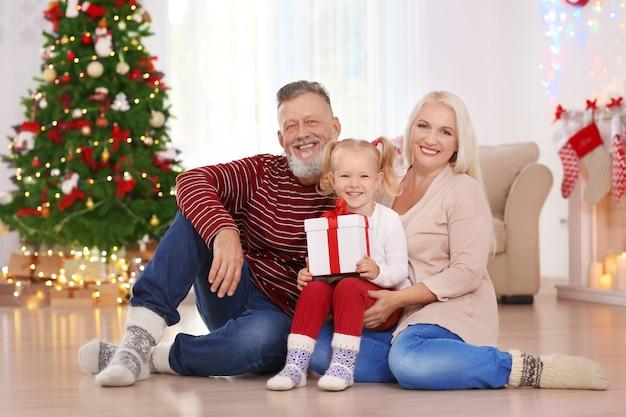 Szczęśliwa para starszych z wnuczką i prezentem świątecznym w domu