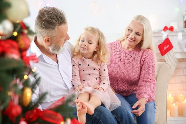 Szczęśliwa para starszych z wnuczką świętującą boże narodzenie w domu