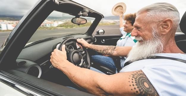 Szczęśliwa para starszych zabawy w kabriolecie podczas letnich wakacji - skup się na twarzy mężczyzny hipster