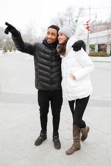 Szczęśliwa para stoi daleko od i wskazuje przy zima parkiem