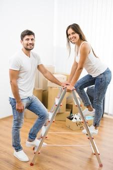 Szczęśliwa para stoi na drabinie na tle kartonowych pudeł