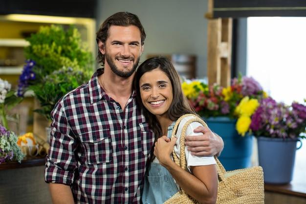 Szczęśliwa para stoi w kwiaciarni