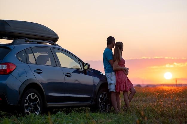 Szczęśliwa para stoi w pobliżu ich samochodu o zachodzie słońca. młody mężczyzna i kobieta, ciesząc się razem, podróżując pojazdem.