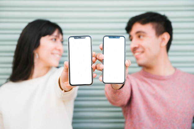 Szczęśliwa para stoi ze smartfonami