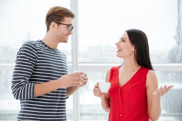 Szczęśliwa para stojąca przy oknie z filiżankami kawy w biurze