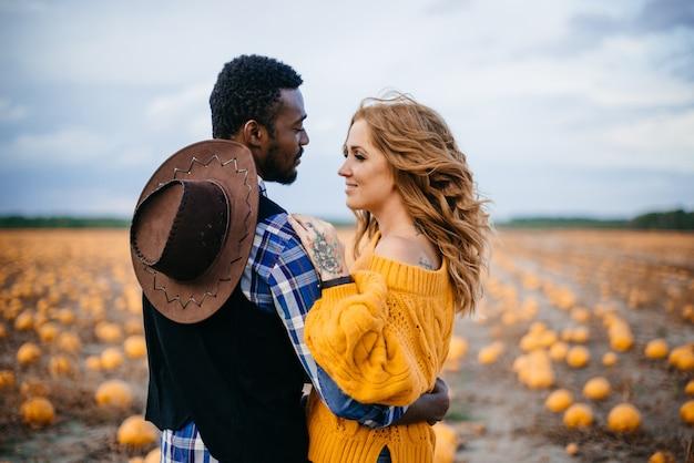 Szczęśliwa para stojący w polu dyni