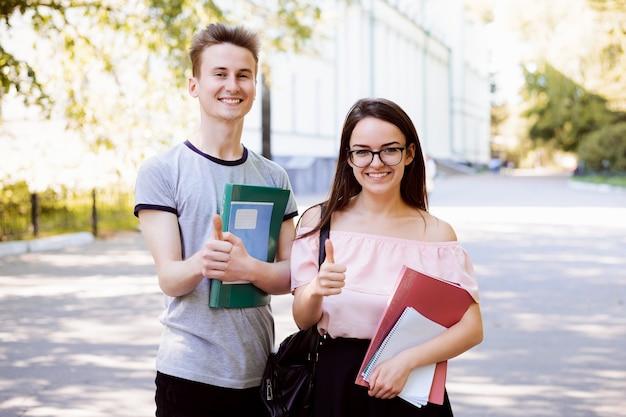 Szczęśliwa para studentów stojących w parku i pokazując kciuki do góry