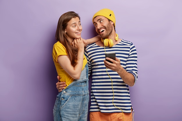 Szczęśliwa para stylowe pozowanie z smartphone