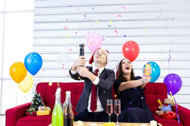 Szczęśliwa para świętuje boże narodzenia z przyjęciem z balonami