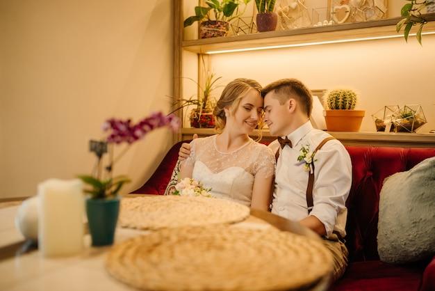Szczęśliwa para świeżo upieczonych wygrzewa się ze sobą w przytulnej kawiarni.