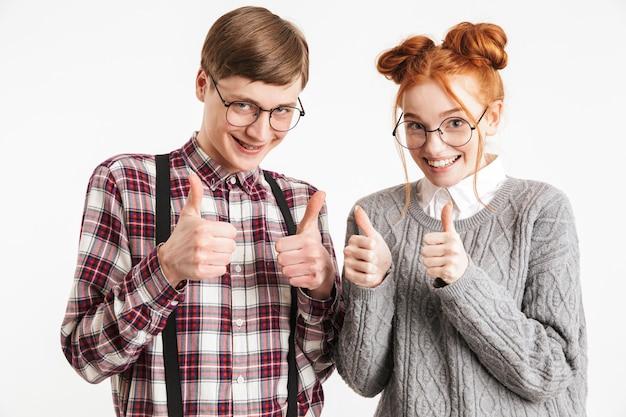 Szczęśliwa para szkolnych frajerów pokazuje kciuki do góry