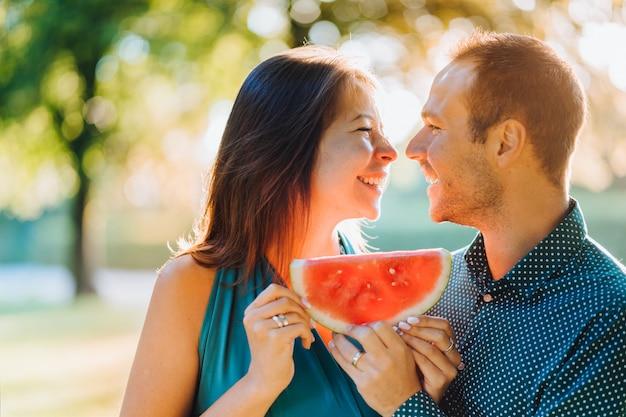 Szczęśliwa para trzyma kawałek arbuza ono uśmiecha się szczęśliwie, cieszący się wakacje w ogródzie przy wschodem słońca. szczęśliwa koncepcja rodziny.