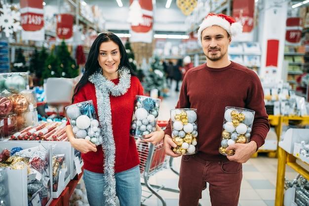 Szczęśliwa para trzyma pudełka z zabawkami świątecznymi w sklepie, tradycja rodzinna. grudniowe zakupy artykułów i dekoracji świątecznych