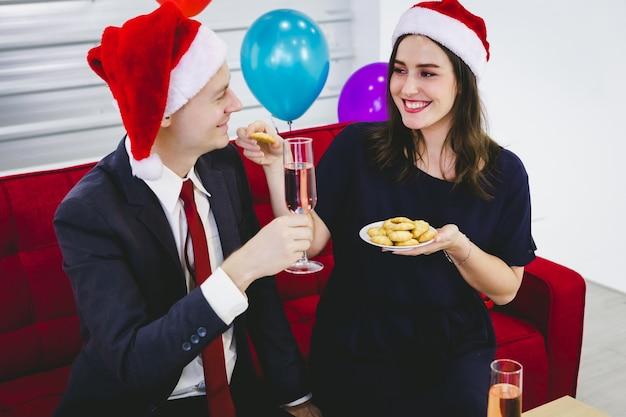 Szczęśliwa para trzymaj kieliszek szampana i jedz ciasteczka na przyjęciu wigilijnym i sylwestrowym