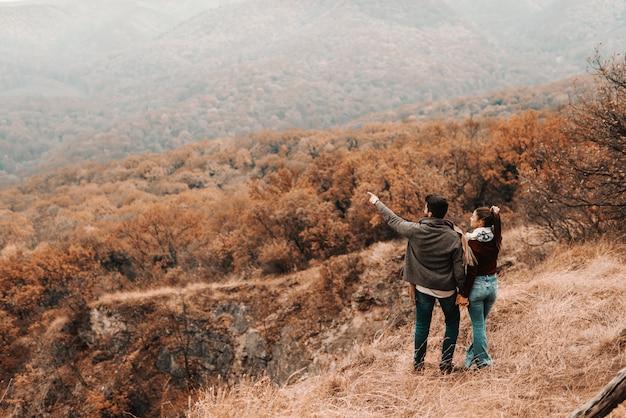 Szczęśliwa para trzymając się za ręce i patrząc na piękny widok. mężczyzna wskazuje na coś. jesienny czas, odwrócony plecami.
