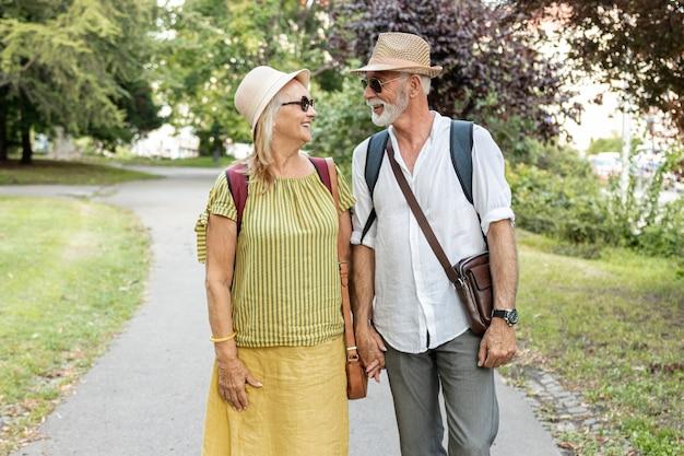 Szczęśliwa para trzymając się za ręce i patrząc na siebie w parku