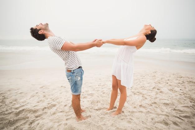 Szczęśliwa para trzymając się za ręce na plaży