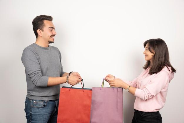 Szczęśliwa para trzymając torby na zakupy na białym tle.