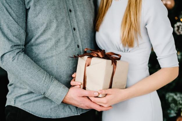 Szczęśliwa para trzymająca prezent przy choince mężczyzna daje kobiecie prezent wesołych świąt