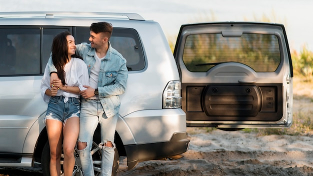 Szczęśliwa para turystów i ich samochód