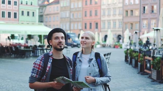 Szczęśliwa para turystów patrząc na główne atrakcje turystyczne za pomocą mapy. są tak szczęśliwi, że mogą zwiedzać.