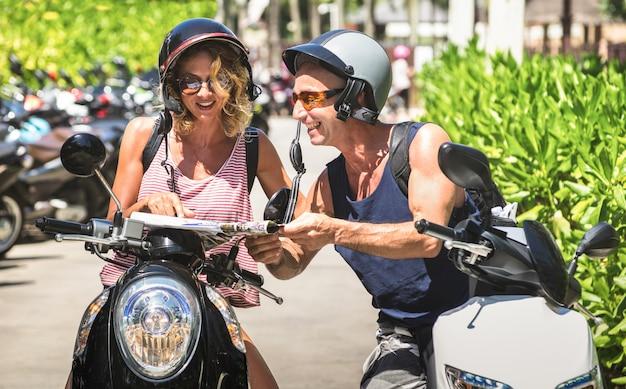 Szczęśliwa para turystów podróżujących po patongu ze skuterem motocyklowym