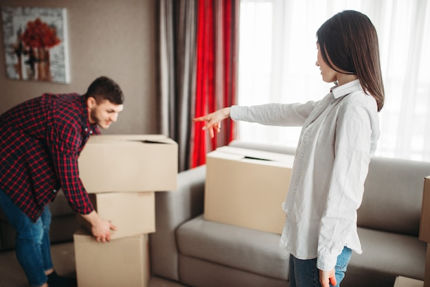 Szczęśliwa para układa kartony w pokoju