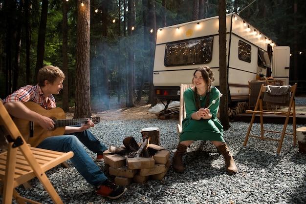 Szczęśliwa para uśmiechnięta kobieta i mężczyzna grający na gitarze siedzi blisko ogniska i przyczepy