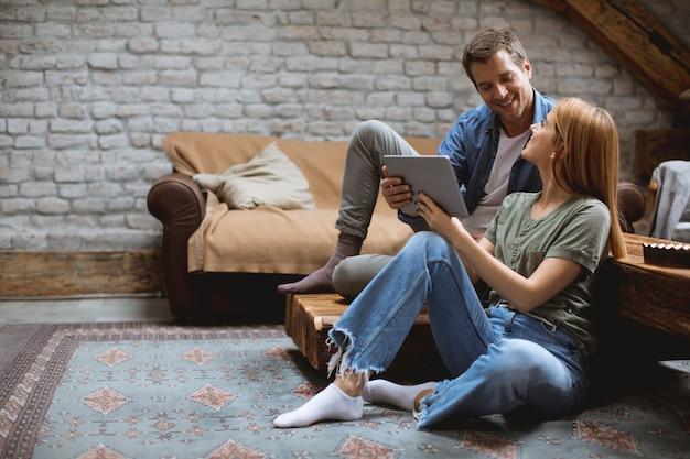 Szczęśliwa para używa cyfrową pastylkę podczas gdy siedzący wpólnie oh podłoga