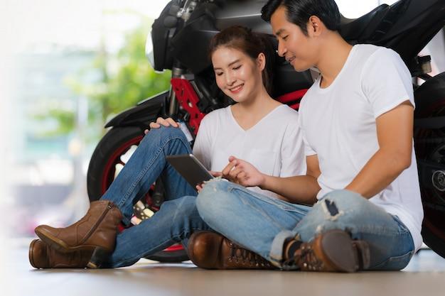 Szczęśliwa para używa cyfrową pastylkę w domu z motocyklu tłem