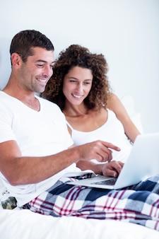 Szczęśliwa para używa laptop na łóżku