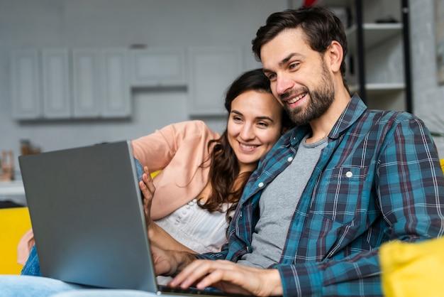 Szczęśliwa para używa laptop