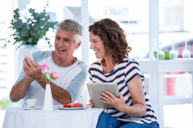 Szczęśliwa para używa telefon komórkowego