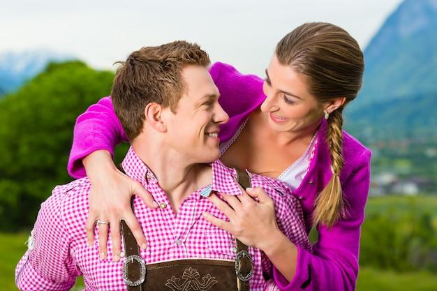 Szczęśliwa para w alpejskiej łące w tracht