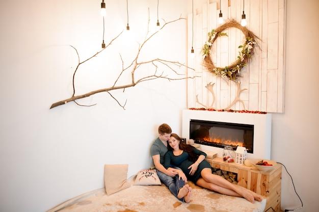 Szczęśliwa para w ciąży leżącego w pobliżu płonącego kominka