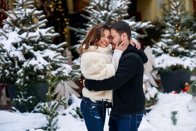 Szczęśliwa para w ciepłe ubrania przytulanie siebie na choinkę z oświetleniem. ferie zimowe, boże narodzenie i nowy rok.
