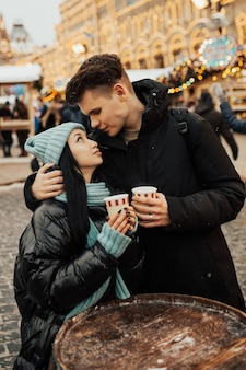 Szczęśliwa para w ciepłych ubraniach picia kawy na jarmarku bożonarodzeniowym