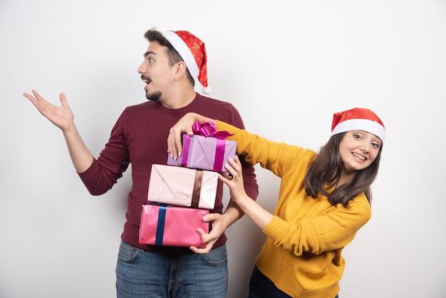 Szczęśliwa para w czapce świętego mikołaja z prezentem na boże narodzenie i nowy rok.