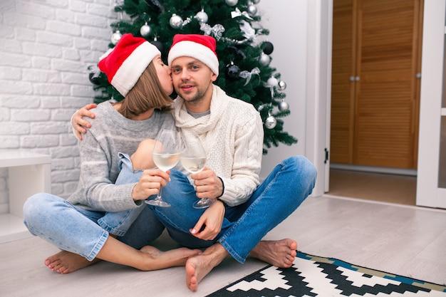 Szczęśliwa para w czapki świąteczne w pobliżu całowania choinki
